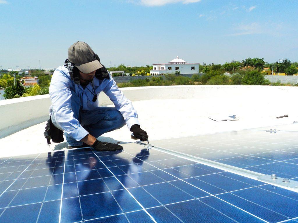 Auf dem Bild ist der Betreiber einer Photovoltaikanlage zu sehen, der seine Anlage für die Inbetriebnahme vorbereitet.